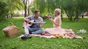 Couplez avoir la date romantique, chansons de chant et jouer la guitare, se reposant dans le parc clips vidéos