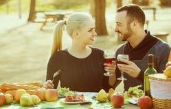 Couplez avoir le pique-nique dans la journée de printemps ensoleillée à la campagne Photographie stock libre de droits