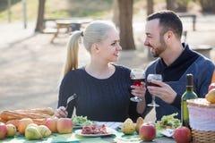Couplez avoir le pique-nique dans la journée de printemps ensoleillée à la campagne Photos libres de droits