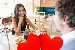 Couplez avoir le repas au restaurant avec les coeurs accrochants rouges Photo libre de droits