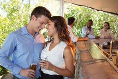 Couplez avoir un verre de bière au compteur dans le restaurant Photographie stock libre de droits