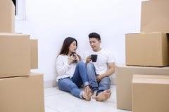 Couplez avoir une pause-café dans la nouvelle maison image stock