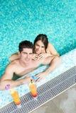 Couplez boire un cocktail par la piscine et la détente Photographie stock