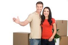 Couplez célébrer la nouvelle maison avec des clés et des boîtes mobiles Image libre de droits