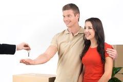 Couplez célébrer la nouvelle maison prenant des clés et des boîtes mobiles Images stock