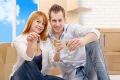 Couplez célébrer leur nouveaux maison, clés et champagne à disposition Photo stock