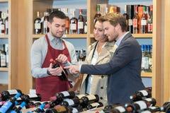 Couplez choisir ensemble le vin de bouteille dans la maison de vin images stock