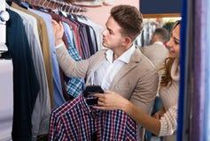 Couplez choisir la nouvelle chemise dans le magasin de tissus de men's Photo libre de droits