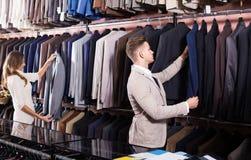 Couplez choisir le nouveau costume dans le magasin de tissus de men's Photographie stock libre de droits
