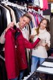 Couplez choisir le nouveau manteau dans le magasin de tissus de men's Photographie stock
