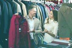 Couplez choisir le nouveau manteau dans le magasin de tissus de men's Images stock