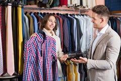 Couplez décider de la nouvelle chemise dans le magasin de tissus de men's Photographie stock libre de droits