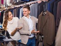 Couplez décider du nouveau costume dans le magasin de tissus de men's Images libres de droits