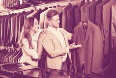 Couplez décider du nouveau costume dans le magasin de tissus de men's Photos libres de droits