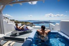 Couplez détendre et contempler la belle scène du pool privé dans un d'Oia, Santorini, Grèce image stock