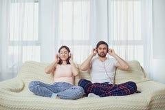 Couplez dans des écouteurs se reposant sur le sofa écoutant la musique dans la chambre images libres de droits