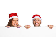 Couplez dans des chapeaux de Santa avec le conseil vide Image stock