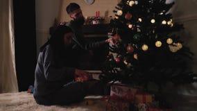 Couplez dans l'amour décorant l'arbre de Noël à la maison La femme corrige l'arc sur le boîte-cadeau Les couples heureux se prépa banque de vidéos