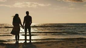 Couplez dans l'amour regardant le coucher du soleil au-dessus de la mer, tenant des mains Jour frais, le vent souffle Vue arrière clips vidéos