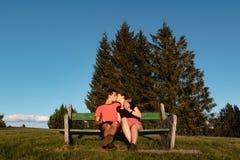 Couplez dans l'amour se reposant sur le banc dans les montagnes et embrassant après une hausse images libres de droits