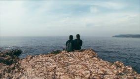 Couplez dans l'amour se reposant sur un bord rocheux par la mer, en parlant sur différents sujets et appréciez la vue Beau timela banque de vidéos