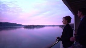 Couplez dans l'amour se tenant sur le balcon de l'hôtel appréciant la vue de la rivière d'hiver Homme étreignant son aimé par clips vidéos