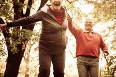 Couplez dans l'habillement de sports jouant et attrapant en parc Photo stock