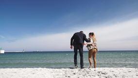 Couplez dans le jeu fonctionnant d'amour sur la plage au jour froid banque de vidéos