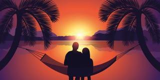 Couplez dans un hamac apprécie le coucher du soleil sur la plage illustration stock