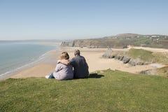 Couplez dehors au-dessus de regarder une vue de paysage de plage Photographie stock