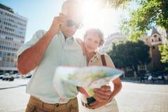 Couplez dehors dans la ville lisant une carte pour la direction Photographie stock