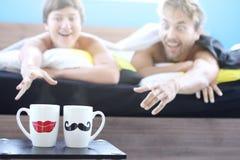 Couplez des amants - l'homme et la femme se sont juste réveillés, mensonge dans le lit et tirent leurs mains avec désir aux tasse photos libres de droits