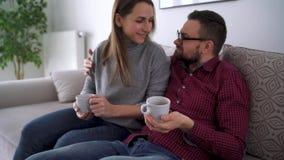 Couplez des amants regardent la télévision a embrassé sur le sofa dans la nouvelle maison et observe un film ensemble Concept de  banque de vidéos
