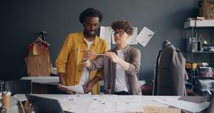 Couplez des concepteurs tirant la photo de prise étendue plate des croquis sur la table de couture banque de vidéos