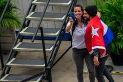 Couplez des Cubains, en portant un drapeau, prenez un selfie dans le consid?rant de Gente de Zona chez Seaworld dans la r?gion in images stock