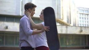 Couplez des planchistes embrassant, visages cachés derrière le conseil, culture secondaire de la jeunesse clips vidéos
