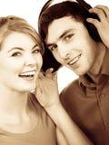 Couplez deux amis avec des écouteurs écoutant la musique Images libres de droits