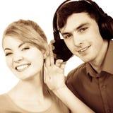 Couplez deux amis avec des écouteurs écoutant la musique Photo stock