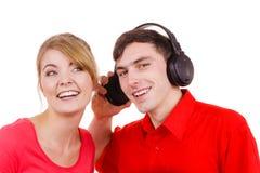 Couplez deux amis avec des écouteurs écoutant la musique Images stock