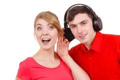 Couplez deux amis avec des écouteurs écoutant la musique Image libre de droits