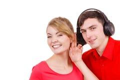 Couplez deux amis avec des écouteurs écoutant la musique Photos stock