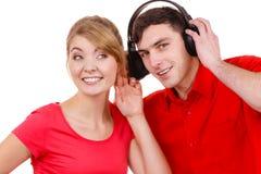 Couplez deux amis avec des écouteurs écoutant la musique Photo libre de droits
