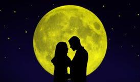 Couplez devant la lune images stock