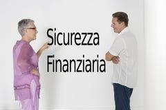 Couplez discuter la sécurité contre le mur blanc avec le texte italien Sicurezza Finanziaria Images stock