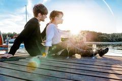 Couplez en champagne potable d'amour sur le dock images libres de droits