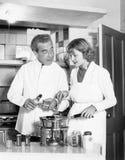Couplez ensemble dans la cuisine préparant une fondue (toutes les personnes représentées ne sont pas plus long vivantes et aucun  photos libres de droits