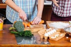 Couplez faire cuire et couper des carottes sur la cuisine Photographie stock