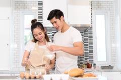 Couplez faire cuire la boulangerie dans la chambre de cuisine, le jeune homme asiatique et la femme ensemble Photo libre de droits