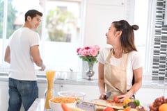Couplez faire cuire la nourriture dans la chambre de cuisine, le jeune homme asiatique et la femme ensemble Image stock