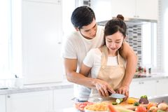 Couplez faire cuire la nourriture dans la chambre de cuisine, le jeune homme asiatique et la femme ensemble Images stock